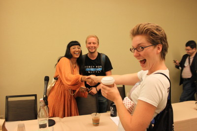 Photo of Isha joyfully greeting conference attendee