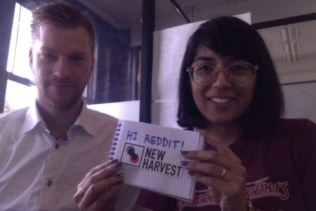 Dan and Isha holding up a sign that says 'Hi Reddit!' above the New Harvest logo